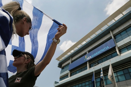 Municipal policewomen hold Greek flags as they protest outside the headquarters of co-ruling New Democracy party during a rally against public sector layoffs the government has promised its international lenders in exchange for bailout funds, in Athens July 11, 2013.