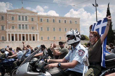 Hundreds of striking municipal police officers drive their motorbikes as a protester holds a Greek national flag during a protest in front of the greek parliament in Athens on July 11, 2013.