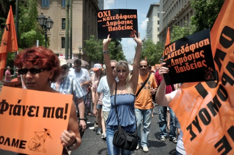 Teachers hold placards reading' no to demolition of public education' and 'its enough'   while  participating in  a protest rally in Athens on July 11, 2013.