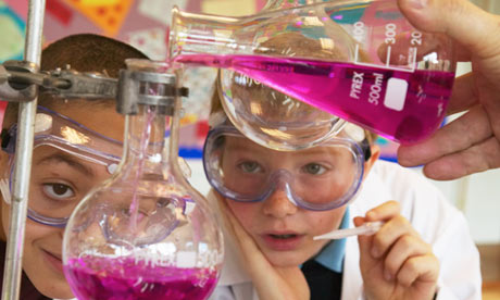 Two schoolboys watching experiment in science classroom