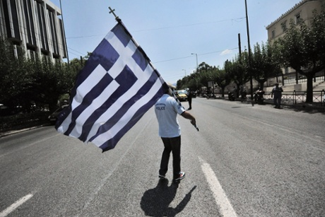 A municipal police officer holds a Greek flag during a protest in front of the  Parliament in Athens, Greece, 15 July 2013