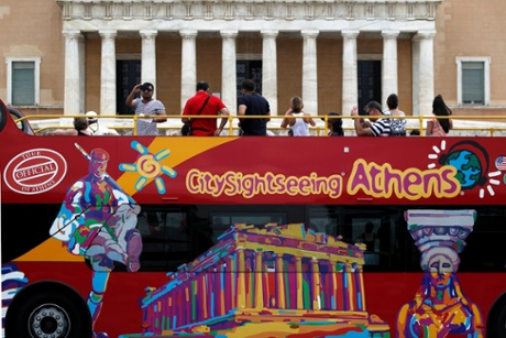 Tourists take photographs from the top of a tourist bus, of protesters taking part in an anti- austerity rally (not seen in the picture) outside the Greek parliament in central Athens,