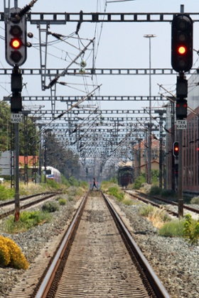 A woman walks across rail tracks in the northern Greek port city of Thessaloniki, during a 24-hour strike that  disrupted flights, public transport, state hospitals and other services, on Tuesday, July 16, 2013.