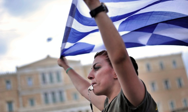 A municipal police officer holds a Greek flag during a protest in front of the parliament in Athens, ahead of tonight's vote. Photograph: EPA/Fotis Plegas G