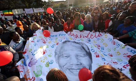 Well-wishers hold a giant banner with an image of Nelson Mandela