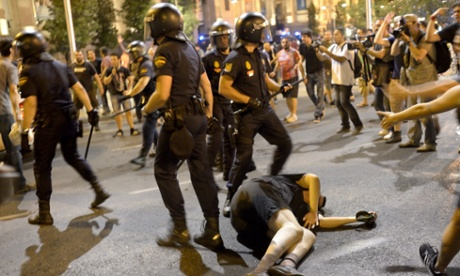Police charge against demonstrators in Madrid as a wounded man lays unconscious on the pavement. Czuko Williams/Demotix/Corbis