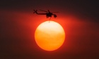 Smoke from the Mountain Fire obscures the sun as a fire fighting helicopter heads to fight the Mountain Fire after picking up water from Lake Hemet near Idyllwild, California.