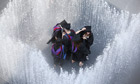 A group of graduates cool off by entering a fountain at the Southbank in London