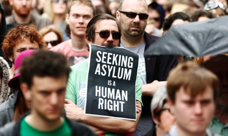A man holds a poster during a raly in support of asylum seekers in central Sydney July 20, 2013.