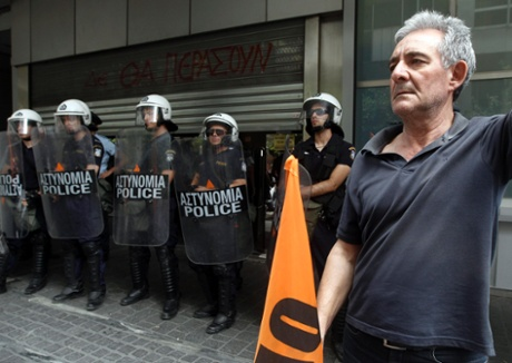 A teacher stands in front of riot police during a protest against public sector reforms and layoffs outside the Finance Ministry in Athens July 22, 2013.