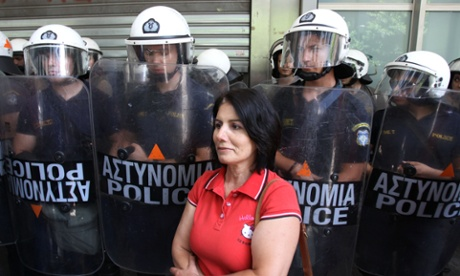 A protesting high-school teacher stands in front of riot police officers outside the Finance Ministry, in central Athens, Monday, July 22, 2013.