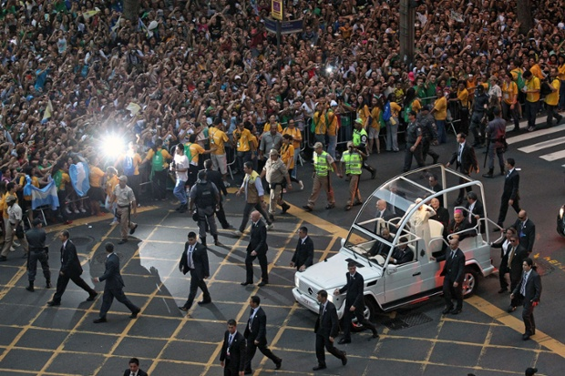 Pope Francis waves from the popemobile on his way to the Guanabara Palace afon. Pope Francis landed in Brazil on for his first overseas trip as pontiff to attend the international festival World Youth Day in Brazil, the world's biggest Catholic country. Photograph: Ari Versiani/AFP/Getty Images