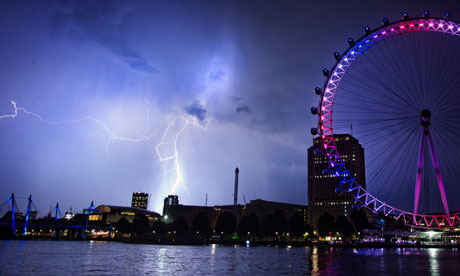 Lightning strikes behind the London Eye, which is red, white and blue to celebrate the royal baby