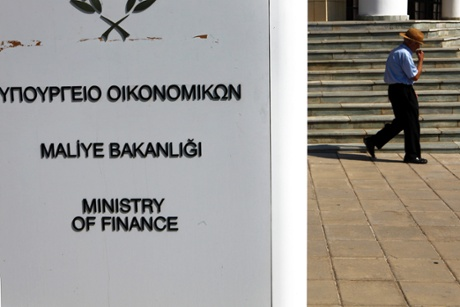 An elderly man walks outside the Ministry of Finance during a meeting between Cyprus' financial minister and central bank government and officials from the European Commission, European Central Bank and the International Monetary Fund in Nicosia, Wednesday, July 17, 2013.