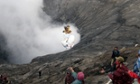A villager uses a net to catch a chicken thrown into the crater of Mount Bromo, Indonesia.