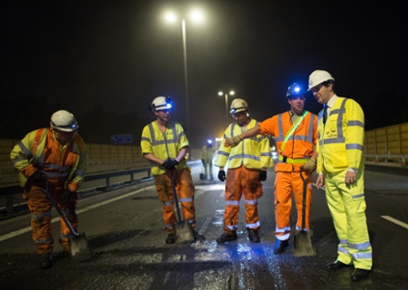 Chancellor of the Exchequer George Osborne meets workers  on a section of the M6 motorway near Birmingham where he saw a road management scheme being constructed whilst the road was closed