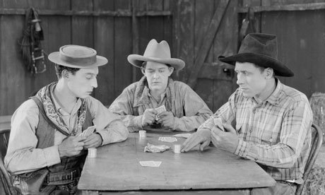 Buster Keaton playing cards with two cowboys in a scene from Go West