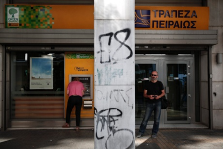 A woman makes a transaction at an ATM of a Piraeus Bank branch as a man waits for his turn in Athens July 25, 2013.