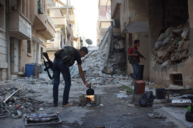 A Free Syrian Army fighter makes tea while a fellow fighter looks inside a building in Deir al-Zor.