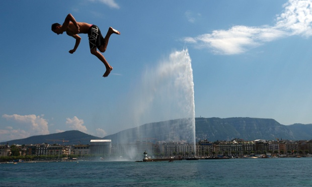 A teenager jumps in the Lake Leman on a hot summer day at the Bains des Paquis in Geneva.