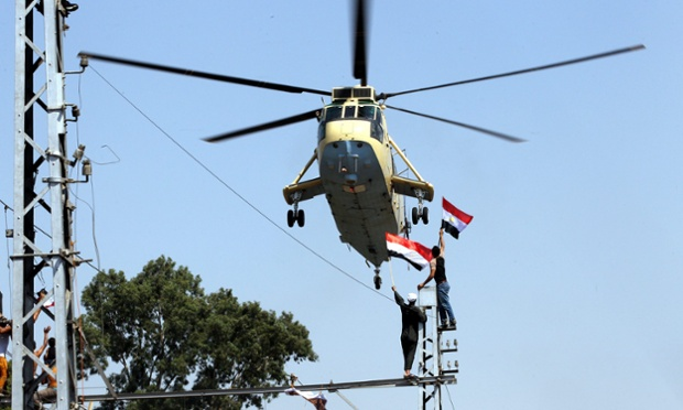 An Egyptian army helicopter hovers, as opponents of ousted president Mohamed Morsi gather at the presidential palace in Cairo. Authorities ordered him to be detained for 15 days pending further investigations on charges of conspiring to carry out 'hostile acts.'