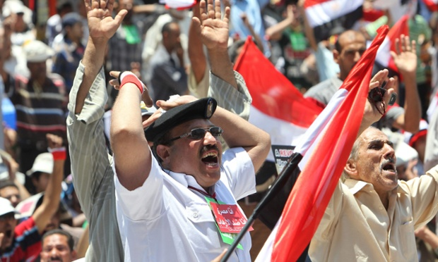 Protesters, including an Egyptian policeman, shout slogans during a protest in support of armed forces, at Tahrir square, Cairo, Egypt
