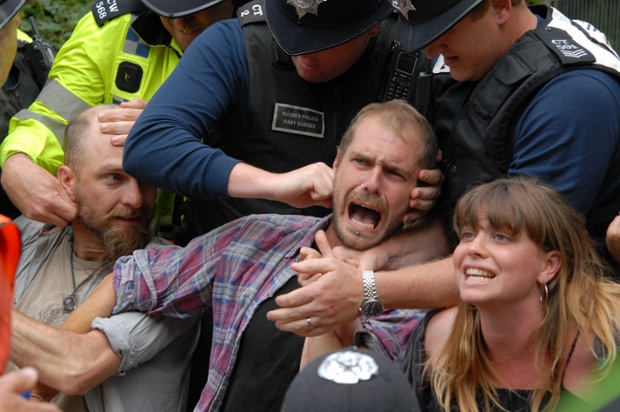 Police using pressure points to force a demonstrator to release his grip from a human chain at an anti-fracking protest at the Cuadrilla  site in Balcombe, Sussex.