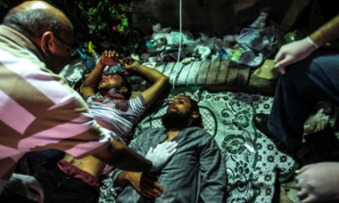 Injured supporters of the deposed Egyptian president Mohamed Morsi receive medical treatment in a makeshift hospital after clashes with riot police in Cairo.