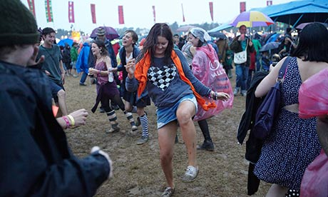 Womad festival goers dance in the rain