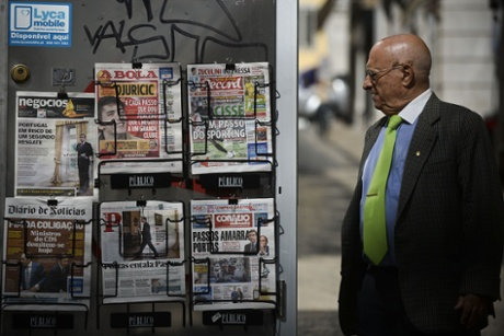 A man looks at daily newspapers with front pages carrying headlines concerning the resignation of Portuguese Foreign Minister and the political crisis in Portugal, in Lisbon on July 3, 2013.