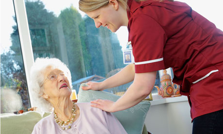 young nurse makes senior woman more comfortable by fluffing up her cushions in care home