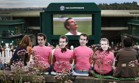 Fans wearing masks depicting Andy Murray watch him lose the first set.