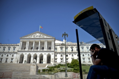 A man waits at a bus stop in front of the Portuguese Parliament in Lisbon on July 3, 2013.