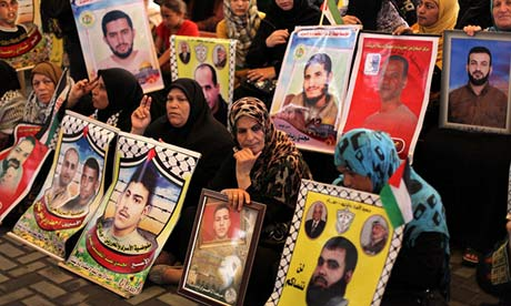 Women hold pictures of Palestinian prisoners of Israel