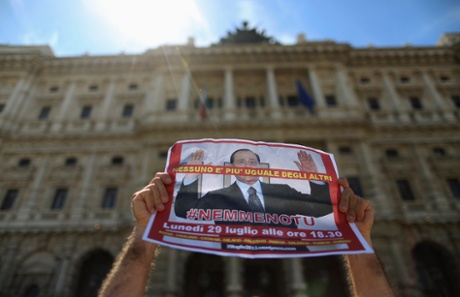 A man holds up a picture of former Italian Prime Minister Silvio Berlusconi as he protests in front of Italy's supreme court building in Rome July 30, 2013.