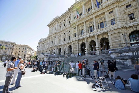 Journalists gather outside the Court of Cassation building where former premier Silvio Berlusconi's case on tax fraud will be decided, in Rome, Tuesday, July 30, 2013.