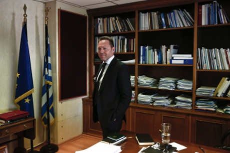 Greece's Finance Minister Yannis Stournaras walks in his office during an interview with Reuters in Athens July 29, 2013.
