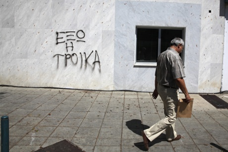 A man walks past a of wall of a Bank of Cyprus branch which has graffiti on it reading in Greek: Troika get out in the Cypriot capital, Nicosia.