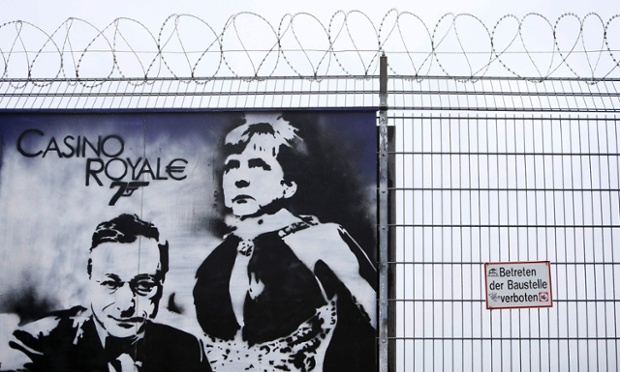 A graffiti depicting European Central Bank (ECB) President Mario Draghi and German Chancellor Angela Merkel is seen outside a fence surrounding the construction site for the new ECB headquarters in Frankfurt, July 3, 2013.