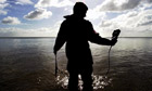 Wading in ... an Environment Agency tester at Dawlish beach in Devon. Photograph: Apex