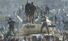 Stone-throwing protesters standing on a tank in Cairo.
