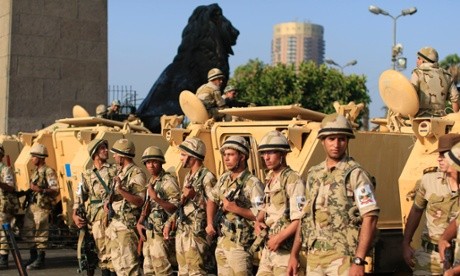 Egyptian army soldiers take their positions near armoured vehicles to guard the entrances of Tahrir Square, in Cairo, Egypt, on 8 July 2013.