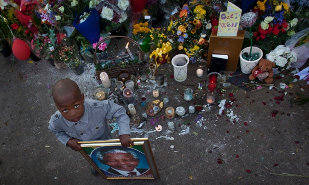 A young boy poses for a photograph holding a portrait of Nelson Mandela next to a wall of get-well messages and flowers laid outside the Mediclinic Heart Hospital where former South African President Nelson Mandela is being treated in Pretoria, South Africa.