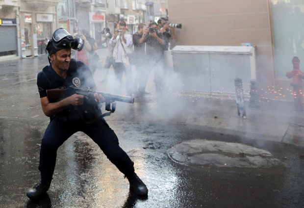 A Turkish riot police officer uses tear gas to disperse protestors during an anti-government protest near Taksim Square in Istanbul. Turkish protestors tried to gather at Gezi Park, which has been the source of protests since 31 May in Istanbul and many other cities across Turkey, after it opened to the public. Photograph: Tolga Bozoglu/EPA