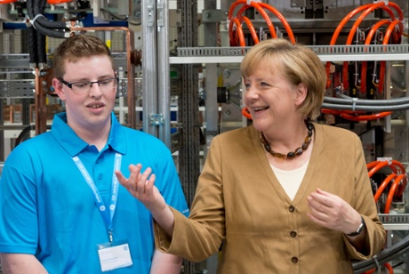 German Chancellor Angela Merkel (CDU) talks to trainee Francis Schwan during a visit of the company GE Energy in Berlin, Germany, 08 July 2013.