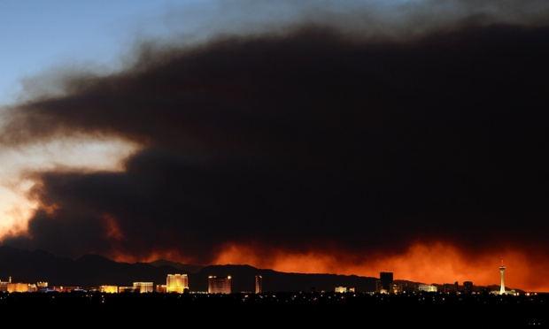 Smoke from the Carpenter 1 fire in the Spring Mountains range is illuminated by the setting sun as it billows behind hotel-casinos on the Las Vegas Strip.