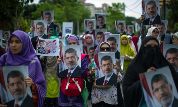 Protesters hold posters of ousted Egyptian President Mohamed Morsi as they oppose the military coup in Egypt, outside the Egyptian embassy in Kuala Lumpur.