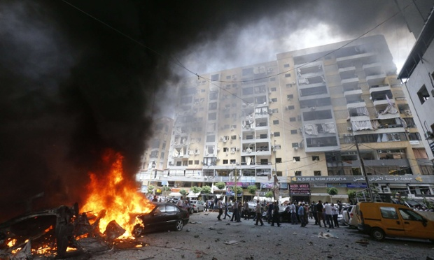Firefighters and residents gather at the site of an explosion in Beirut's southern suburb neighbourhood of Bir al-Abed, after a car bomb wounded at least 18 people.