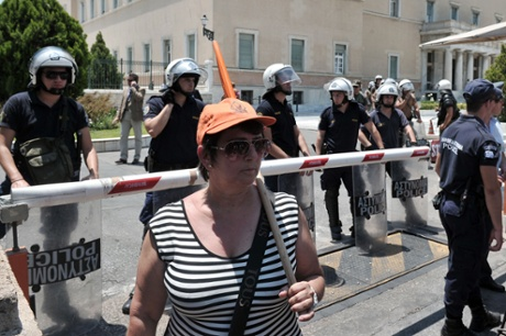 A striking municipal worker stands on July 9, 2013 in front of police forces protecting the Greek Parliament in Athens.