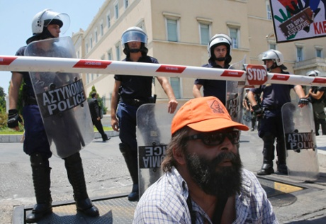 A municipal worker sits in front of riot police guarding the parliament during a rally against public sector reforms in Athens July 9, 2013.
